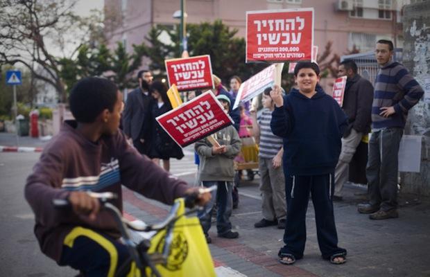 Des habitants de Tel-Aviv brandissent des pancartes « Retournez chez vous » en direction d'un jeune garçon noir. Crédit Photo -- Oren Ziv / ActiveStills